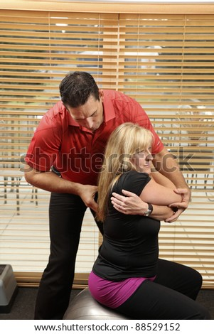 Chiropractor adjusting a patient sitting on a ball - stock photo