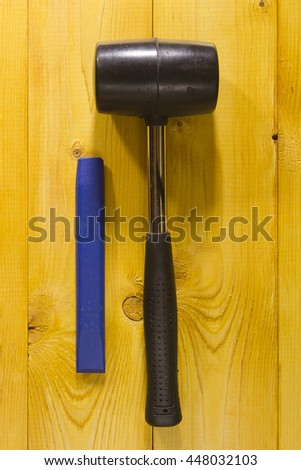 Chisel and black rubber hammer on a brown wooden background