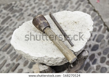 Chisel and hammer stone working, detail of ancient craft with stone carving and shaping the stone - stock photo