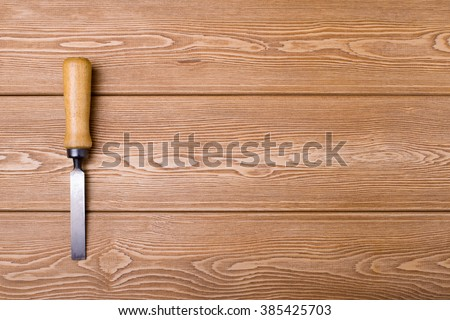 Chisel on wood background