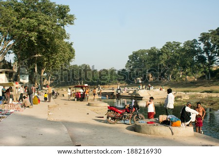 CHITRAKOOT, INDIA - DEC 28: Village poor men have rest near the river bank in the rural landscape on December 28, 2012. Population of Chitrakoot is 22,294. By the legend, Lord Rama lived here  - stock photo