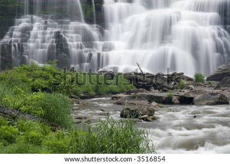 Chittenango Falls in Central New York state. This beautiful waterfall tumbles across many rock ledges creating a beautiul scene and an almost tropical setting with the lush green plant foilage. - stock photo