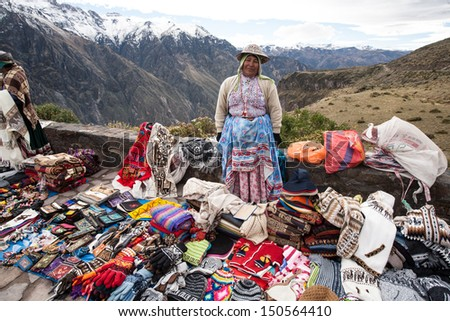 CHIVAY, AREQUPA, PERU - CIRCA 2013:An unidentified  woman sell hand crafts in outdoors circa 2013 in Chivay, Arequipa, Peru. Many women work selling handicrafts in Peru  - stock photo