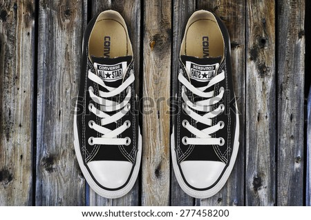 CHLUMCANY, CZECH REPUBLIC, MARCH 27, 2015: Black low Converse shoes on wooden planks - stock photo