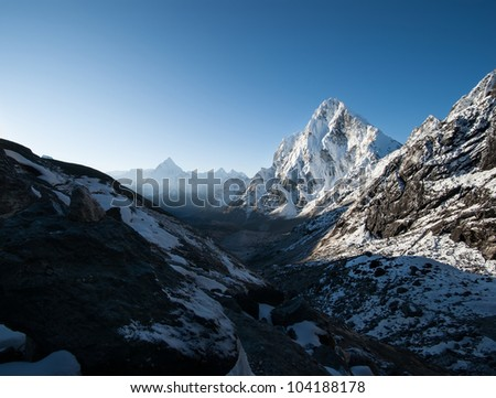 Cho La pass and snowed peaks at dawn in Himalayas. Climbing in Nepal - stock photo