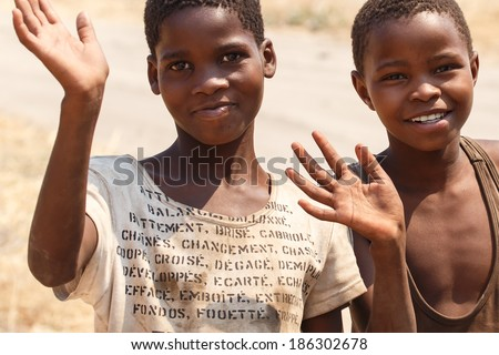 CHOBE, BOTSWANA - OCTOBER 5 2013: Poor African children wander through the desert like Chobe National Park. This year was declared as a drought year by the government in Botswana, Africa - stock photo