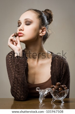 Chocolate addiction, moody portrait of gorgeous brunette with chocolate pralines. - stock photo