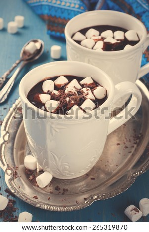 Chocolate almond milk with chocolate and marshmallow on blue background. Retro style toned. Selective focus - stock photo