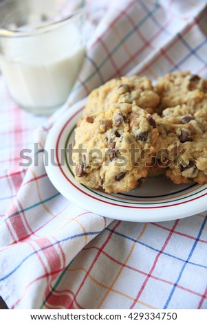 Chocolate and butterscotch chip cookies on a colorful dish with glass of milk on multicolored dish cloth - stock photo
