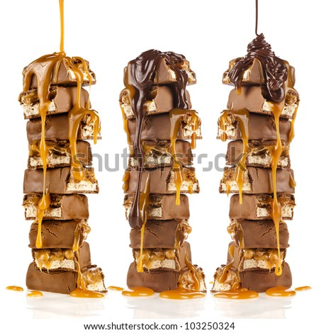 Chocolate and caramel syrup poured on stack of chocolate pieces isolated on white background