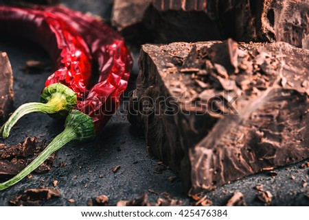 Chocolate and Chili. Black chocolate and chili pepper. Dark chocolate with red chili pepper. Blocks Bitter chocolate with chili on a spoon spill. - stock photo