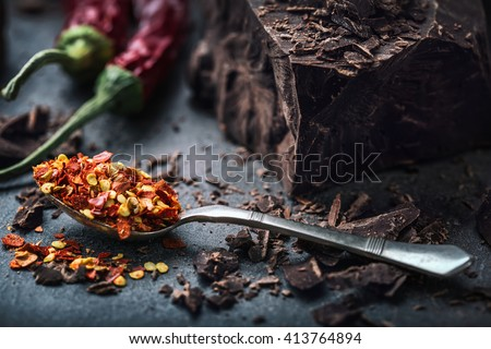 Chocolate and Chili. Black chocolate and chili pepper. Dark chocolate with red chilli pepper. Blocks Bitter chocolate with chili on a spoon spill. - stock photo