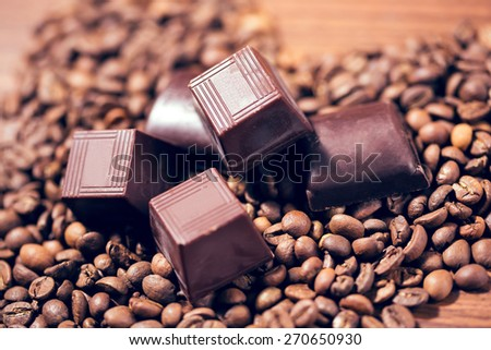 Chocolate and coffee beans on wooden table - stock photo