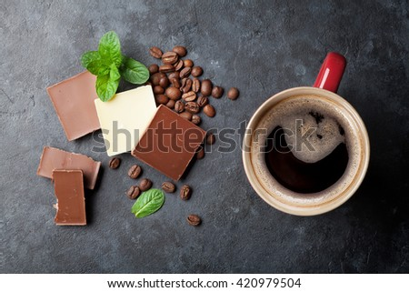 Chocolate and coffee cup on dark stone table. Top view - stock photo