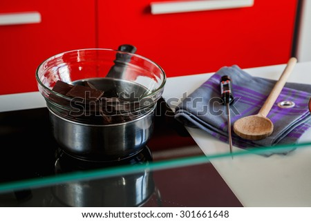 Chocolate And Equipment For Tempering Chocolate On Kitchen Table - stock photo