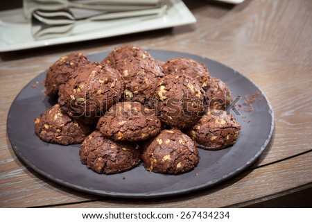 Chocolate and nut cookies on wooden table. Shallow DOF and lightly toned. - stock photo