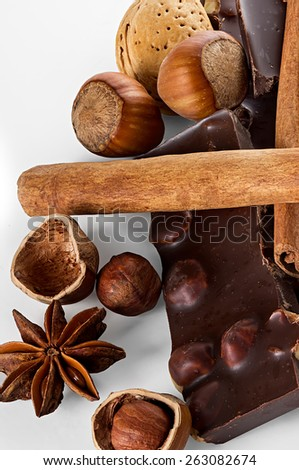 Chocolate and nuts with cinnamon sticks, star anise - stock photo
