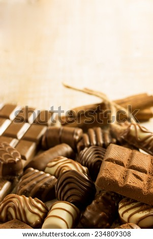 chocolate and pralines with cocoa and cinnamon on a wooden background - stock photo