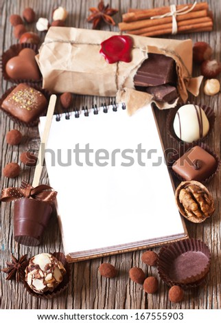 Chocolate and spices frame with notebook for text on a wooden background.