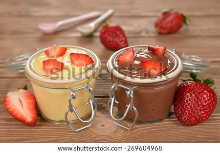Chocolate and vanilla pudding with strawberries on a brown background - stock photo