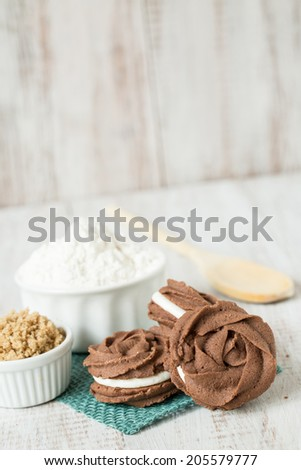 Chocolate and vanilla sandwich cookies with flour and brown sugar and wood spoon
