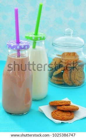 Chocolate and white milk with ginger cookies in vertical format and shot in natural light