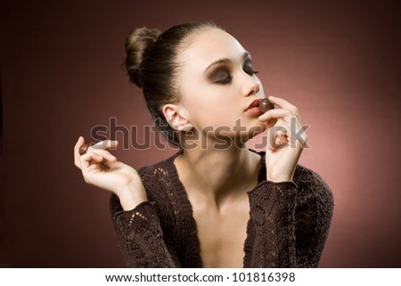 Chocolate art, artistic portrait of beautiful young brunette with bonbons. - stock photo