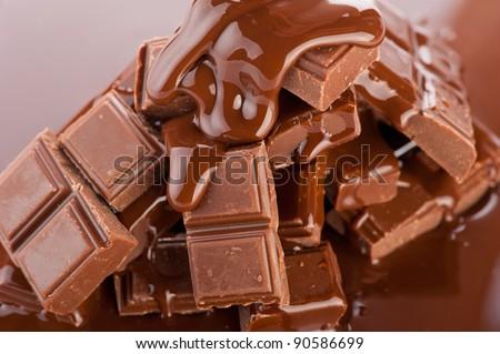 Chocolate background. Broken bars and flowing liquid chocolate - stock photo