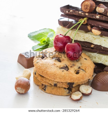 Chocolate background - different types of chocolate, cookies, candies, nuts, mint, cherry, white wood background, closeup - stock photo