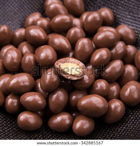 Chocolate ball candy smarties on black background with nuts inside