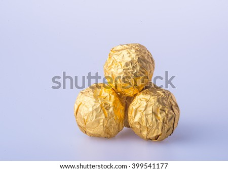 Chocolate ball in a gold foil paper on a background