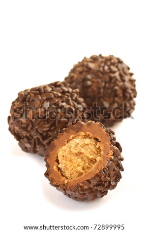 Chocolate balls and a half with praline filling isolated on white.