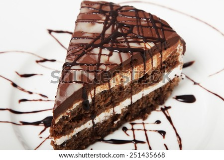 Chocolate banana cake on a white plate. Biscuit cake. Gentle melting texture of chocolate sponge cake with layers of banana and a light vanilla cream, under the glaze of dark and white chocolate. - stock photo