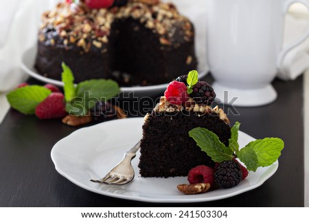 Chocolate banana cake with nuts decorated with berries - stock photo