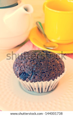 Chocolate banana cupcake on white dish (Process effect in vintage style on this photo)