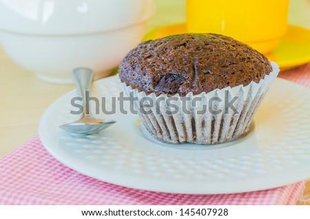 Chocolate banana cupcake on white dish with teapot&yellow tea cup - stock photo