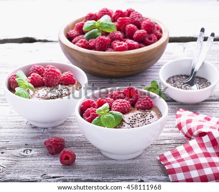 Chocolate banana smoothies with chia seeds served ripe raspberries and fresh mint on a light wooden background. The white ceramic bowls of serving a healthy breakfast. selective focus