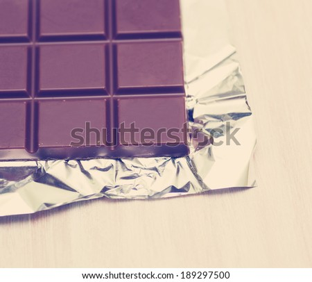 chocolate bar in foil lying on the table - stock photo