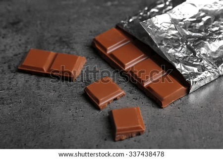 Chocolate bar in foil  on gray background - stock photo