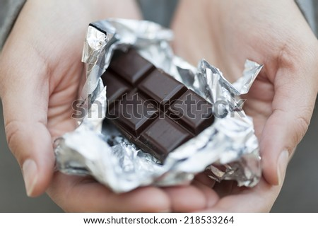 Chocolate bar in silver foil in woman's palms. - stock photo