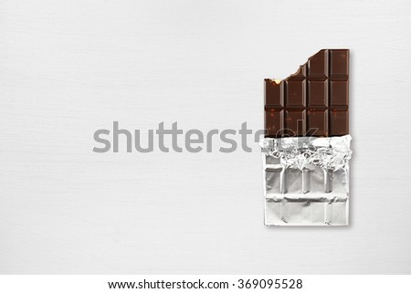 Chocolate bar on white wooden table