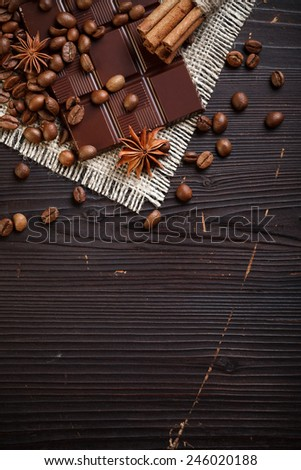 Chocolate bar with aromatic spices and coffee beans on wooden table - stock photo