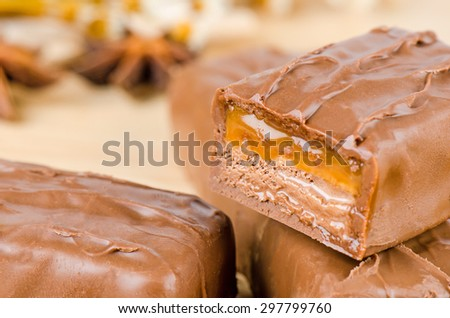 Chocolate bar with caramel toffee on wooden background. - stock photo
