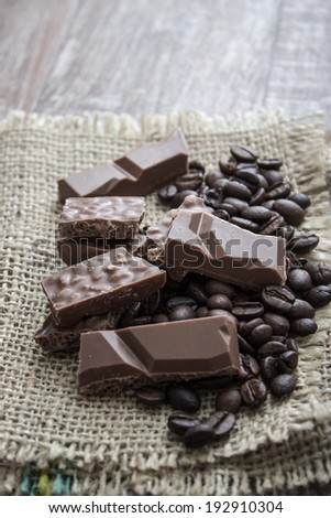 chocolate bars and coffee beans  on wooden table, close up - stock photo