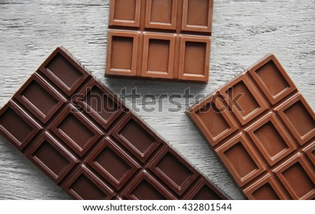 Chocolate bars  on wooden background - stock photo