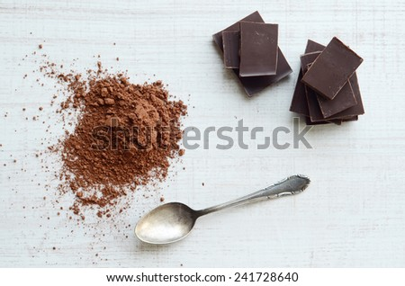 Chocolate bars with heap of cacao powder