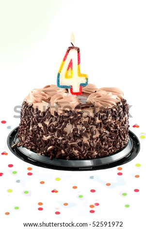 Chocolate birthday cake surrounded by confetti with lit candle for a fourth birthday or anniversary celebration - stock photo