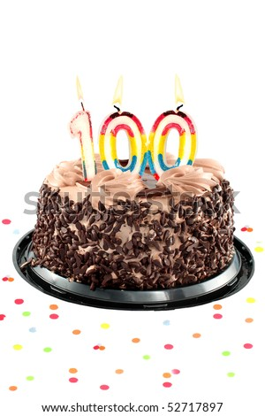 Chocolate birthday cake surrounded by confetti with lit candles for a century, one hudredth birthday or anniversary celebration - stock photo