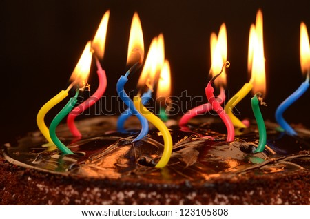 Chocolate birthday cake with candles lit. - stock photo