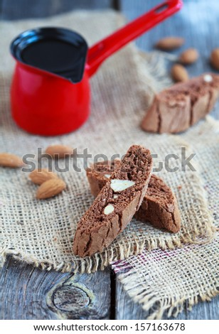 Chocolate biscotti with almonds and red coffee pot on a wooden table in rustic style, Selective focus on lower biscotti - stock photo